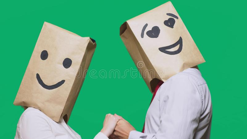Concept of emotions, gestures. a couple of people with paper bags on their heads, with a painted emoticon, smile, joy. Eyes in love royalty free stock photography