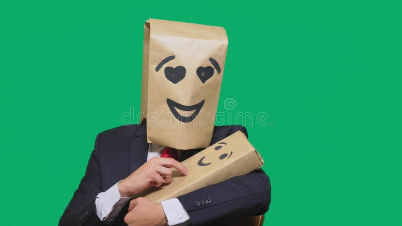Concept of emotions, gestures. a man with a package on his head, with a painted emoticon, smile, enamored eyes. plays. With the child painted on the box stock photography