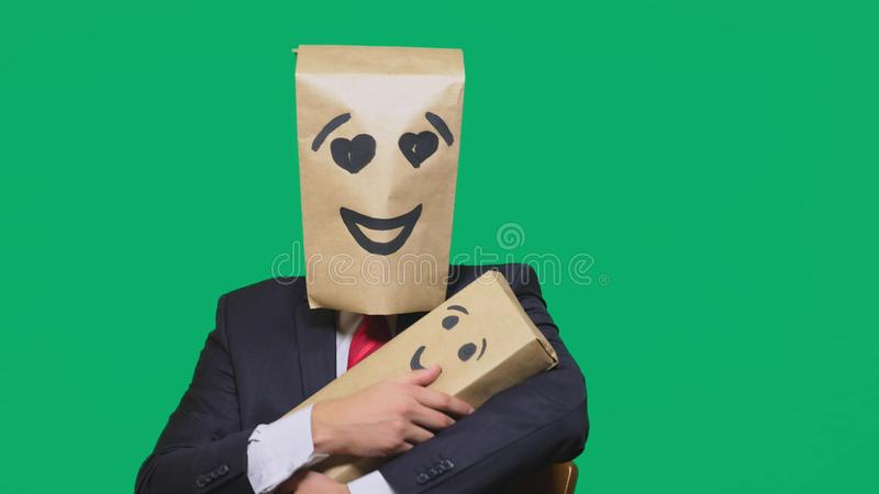 Concept of emotions, gestures. a man with a package on his head, with a painted emoticon, smile, enamored eyes. plays. With the child painted on the box royalty free stock photo