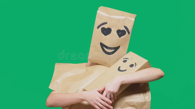 Concept of emotions, gestures. a man with a package on his head, with a painted emoticon, smile, enamored eyes. plays. With the child painted on the box stock images