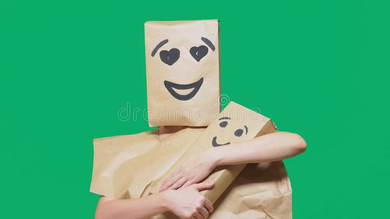Concept of emotions, gestures. a man with a package on his head, with a painted emoticon, smile, enamored eyes. plays. With the child painted on the box stock photo