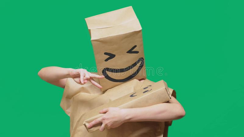 Concept of emotions, gestures. man with a package on his head, with a painted emoticon, smile, joy, laughter. plays with. The child painted on the box stock photo