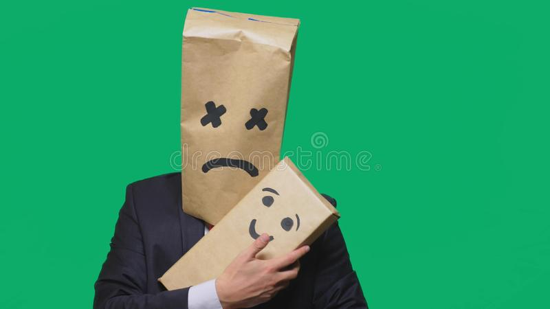 Concept of emotions, gestures. man with a package on his head, with a painted emoticon, smile, joy, laughter. plays with. The child painted on the box royalty free stock photography
