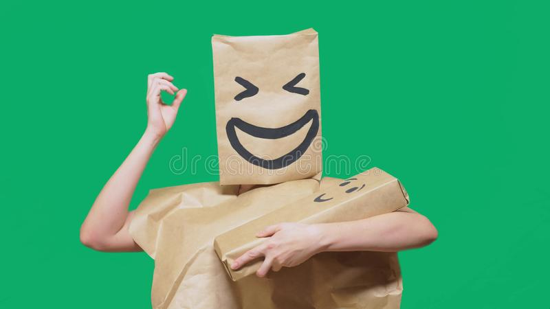 Concept of emotions, gestures. man with a package on his head, with a painted emoticon, smile, joy, laughter. plays with. The child painted on the box royalty free stock image