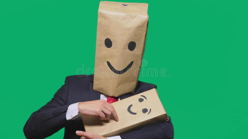 Concept of emotions, gestures. man with a package on his head, with a painted emoticon, smile, joy, laughter. plays with. The child painted on the box royalty free stock photos