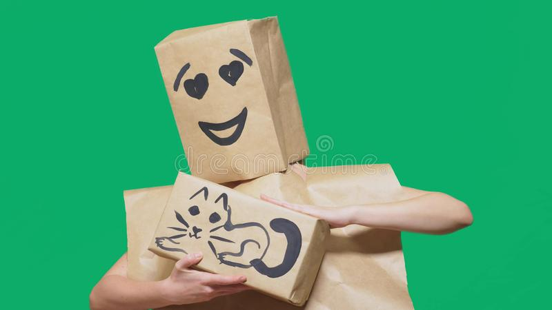 Concept of emotions, gestures. a man with a package on his head, with a painted emoticon, smile, loving eyes. plays with. A cat drawn on the box royalty free stock photography