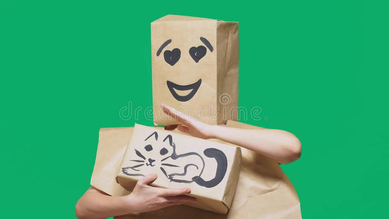 Concept of emotions, gestures. a man with a package on his head, with a painted emoticon, smile, loving eyes. plays with. A cat drawn on the box stock images