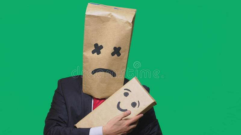 Concept of emotions, gestures. a man with a package on his head, with a painted emoticon, tired, sleepy. plays with the. Child painted on the box royalty free stock image