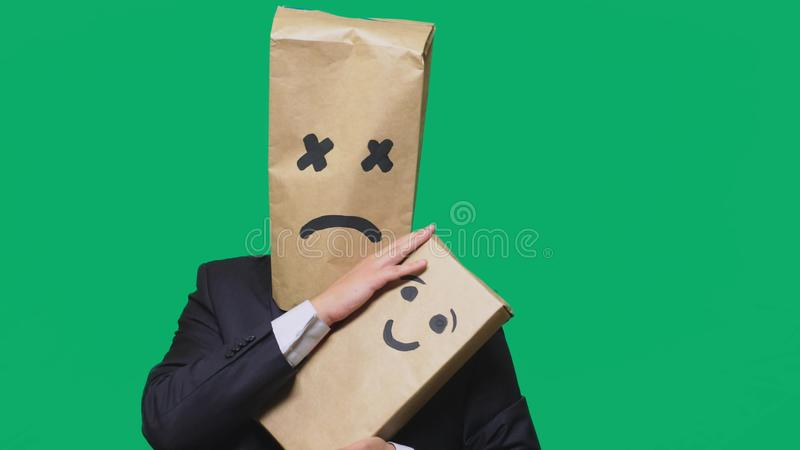 Concept of emotions, gestures. a man with a package on his head, with a painted emoticon, tired, sleepy. plays with the. Child painted on the box royalty free stock photos