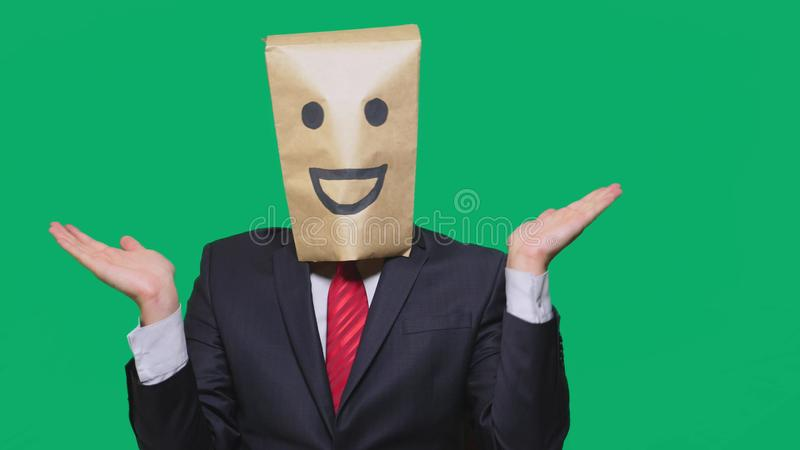Concept of emotions, gestures. a man with paper bags on his head, with a painted emoticon, smile, joy.  stock photography