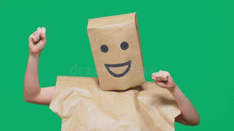 Concept of emotions, gestures. a man with paper bags on his head, with a painted emoticon, smile, joy.  stock photos