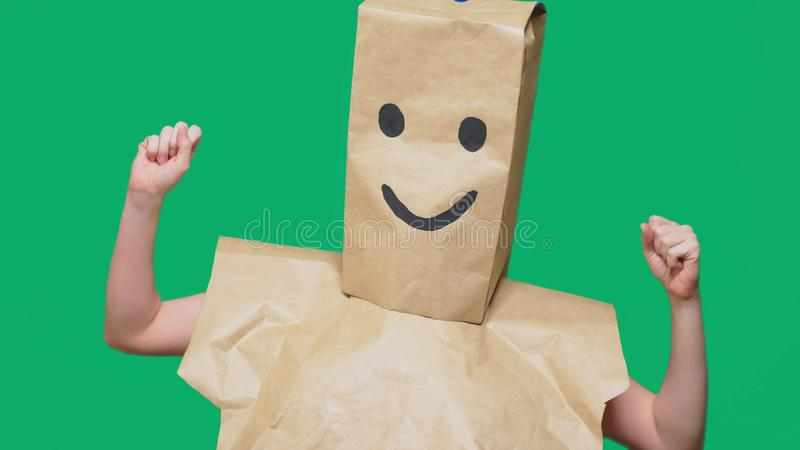 Concept of emotions, gestures. a man with paper bags on his head, with a painted emoticon, smile, joy.  royalty free stock photos