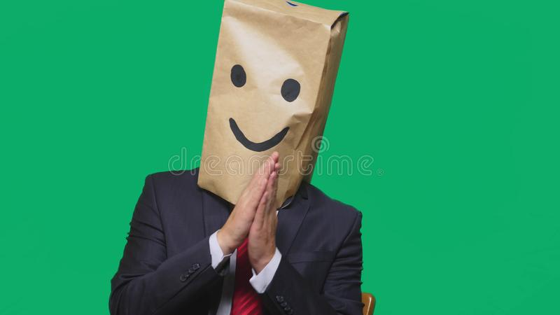 Concept of emotions, gestures. a man with paper bags on his head, with a painted emoticon, smile, joy.  royalty free stock photo
