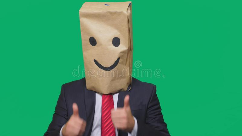 Concept of emotions, gestures. a man with paper bags on his head, with a painted emoticon, smile, joy.  royalty free stock image