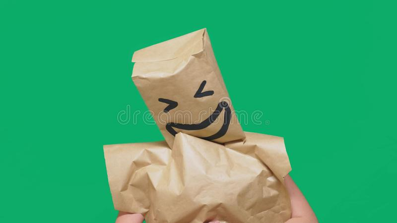 Concept of emotions, gestures. a man with paper bags on his head, with a painted emoticon, smile, joy.  royalty free stock images