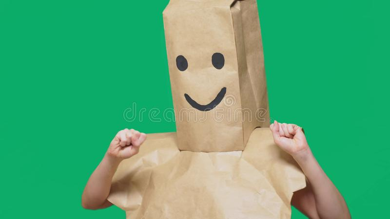Concept of emotions, gestures. a man with paper bags on his head, with a painted emoticon, smile, joy.  stock images