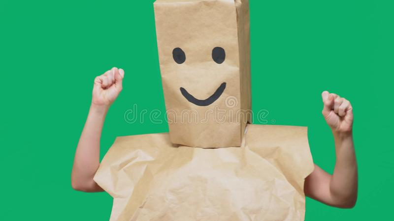 Concept of emotions, gestures. a man with paper bags on his head, with a painted emoticon, smile, joy.  stock image