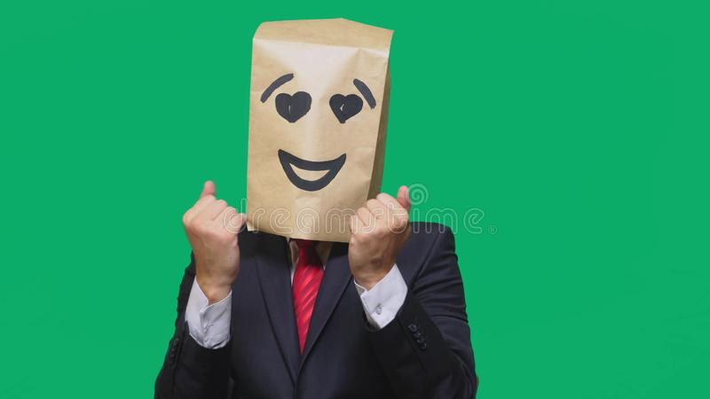 Concept of emotions, gestures. a man with paper bags on his head, with a painted emoticon, smile, joy, love eyes. Concept of emotions, gestures. a man with stock photos