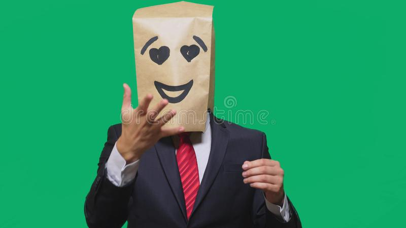 Concept of emotions, gestures. a man with paper bags on his head, with a painted emoticon, smile, joy, love eyes. Concept of emotions, gestures. a man with stock image