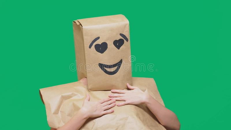 Concept of emotions, gestures. a man with paper bags on his head, with a painted emoticon, smile, joy, love eyes. Concept of emotions, gestures. a man with stock photo