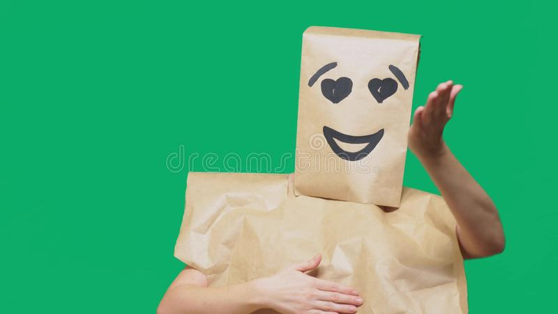 Concept of emotions, gestures. a man with paper bags on his head, with a painted emoticon, smile, joy, love eyes. Concept of emotions, gestures. a man with royalty free stock photo