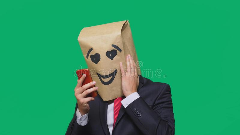 Concept of emotions, gestures. a man with paper bags on his head, with a painted emoticon, smile, joy, love. talking on. A cell phone stock photo