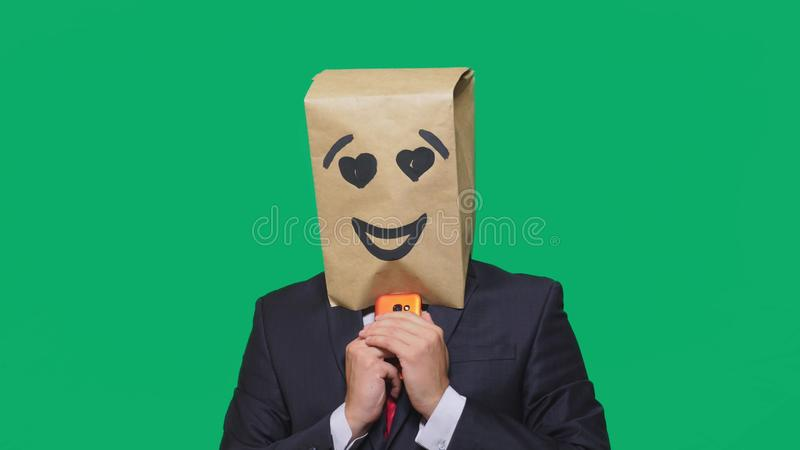 Concept of emotions, gestures. a man with paper bags on his head, with a painted emoticon, smile, joy, love. talking on. A cell phone royalty free stock image