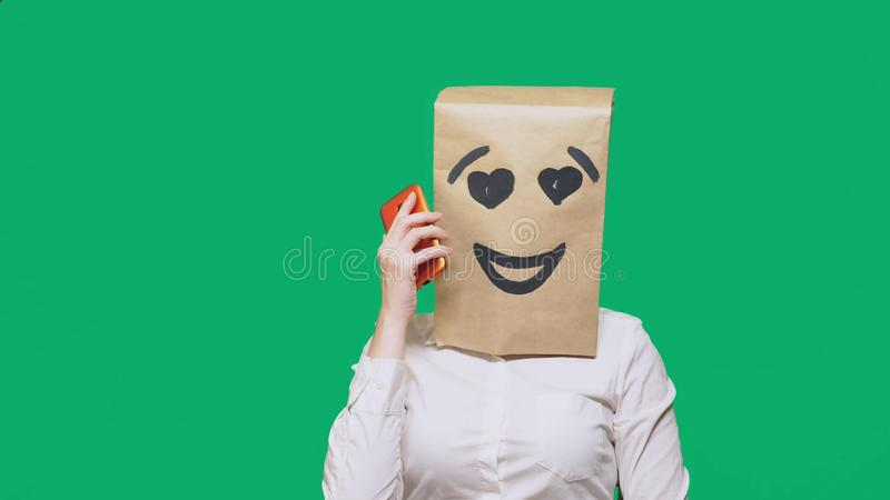 Concept of emotions, gestures. a man with paper bags on his head, with a painted emoticon, smile, joy, love. talking on. A cell phone royalty free stock photography