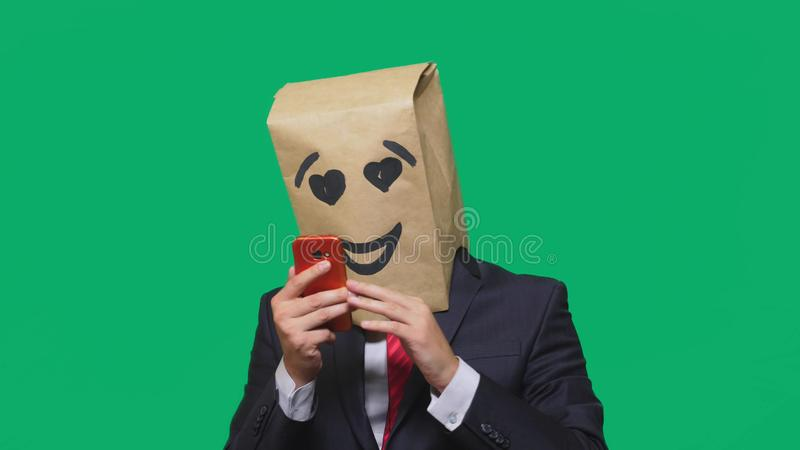 Concept of emotions, gestures. a man with paper bags on his head, with a painted emoticon, smile, joy, love. talking on. A cell phone royalty free stock photo