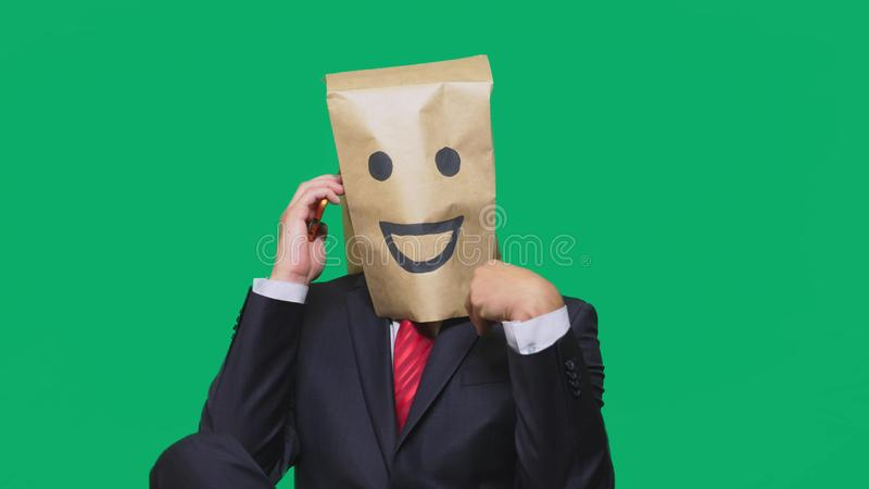 Concept of emotions, gestures. a man with paper bags on his head, with a painted emoticon, smile, joy. talking on a cell. Phone royalty free stock photography