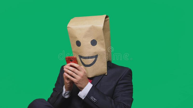 Concept of emotions, gestures. a man with paper bags on his head, with a painted emoticon, smile, joy. talking on a cell. Phone stock image