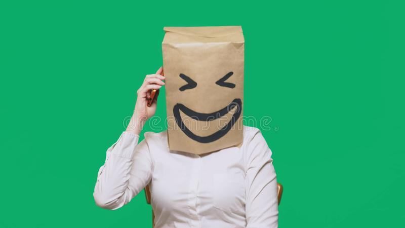 Concept of emotions, gestures. a man with paper bags on his head, with a painted emoticon, smile, joy. talking on a cell. Phone royalty free stock image