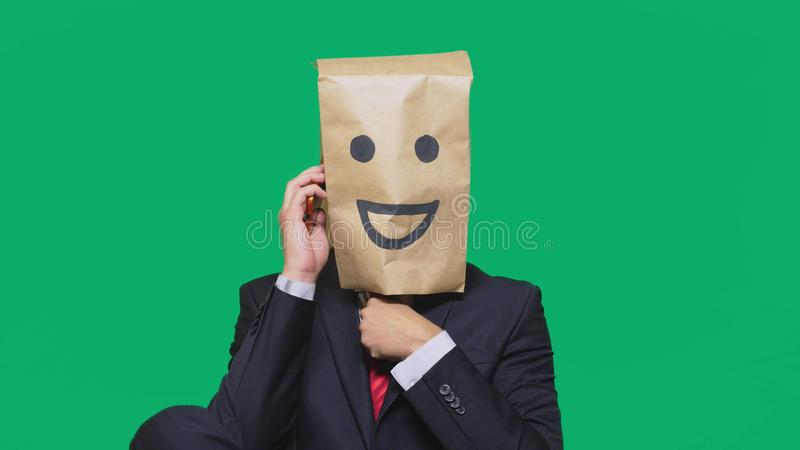 Concept of emotions, gestures. a man with paper bags on his head, with a painted emoticon, smile, joy. talking on a cell. Phone royalty free stock photo