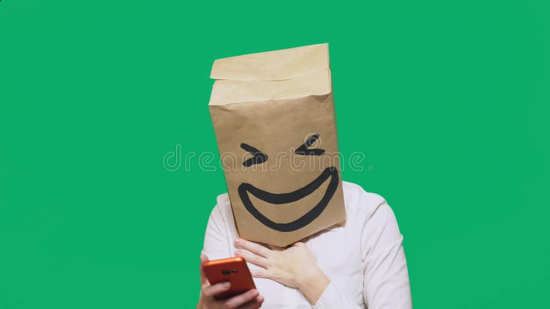 Concept of emotions, gestures. a man with paper bags on his head, with a painted emoticon, smile, joy. talking on a cell. Phone stock photos