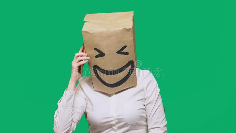 Concept of emotions, gestures. a man with paper bags on his head, with a painted emoticon, smile, joy. talking on a cell. Phone royalty free stock images