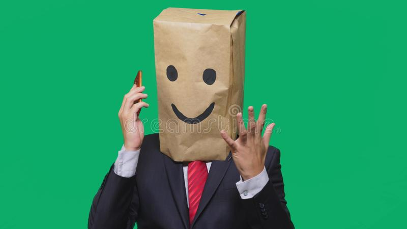 Concept of emotions, gestures. a man with paper bags on his head, with a painted emoticon, smile, joy. talking on a cell. Phone stock photography