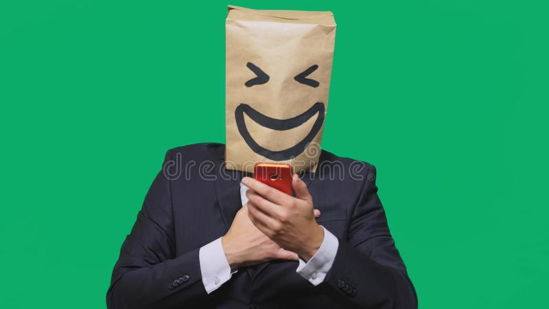 Concept of emotions, gestures. a man with paper bags on his head, with a painted emoticon, smile, joy. talking on a cell. Phone stock images