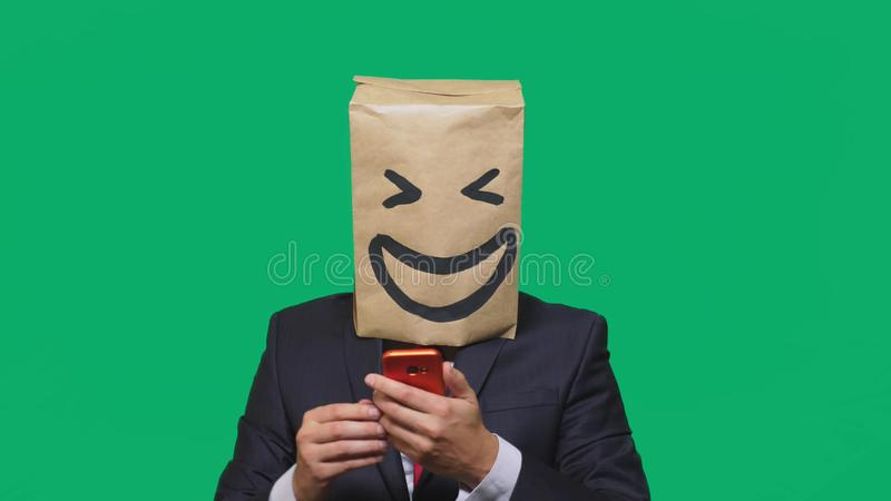 Concept of emotions, gestures. a man with paper bags on his head, with a painted emoticon, smile, joy. talking on a cell. Phone stock photo