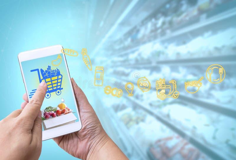 Concept en ligne d'?picerie : Main de femme jugeant le t?l?phone intelligent pour la nourriture de commande ? l'?cran avec des m? images libres de droits