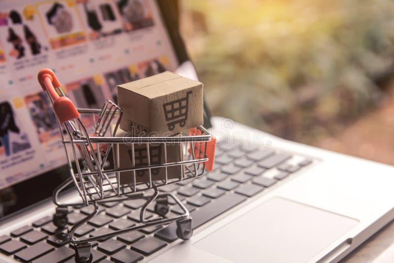 Concept en ligne de achat - cartons de colis ou de papier avec un logo de caddie dans un chariot sur un clavier d'ordinateur port image libre de droits