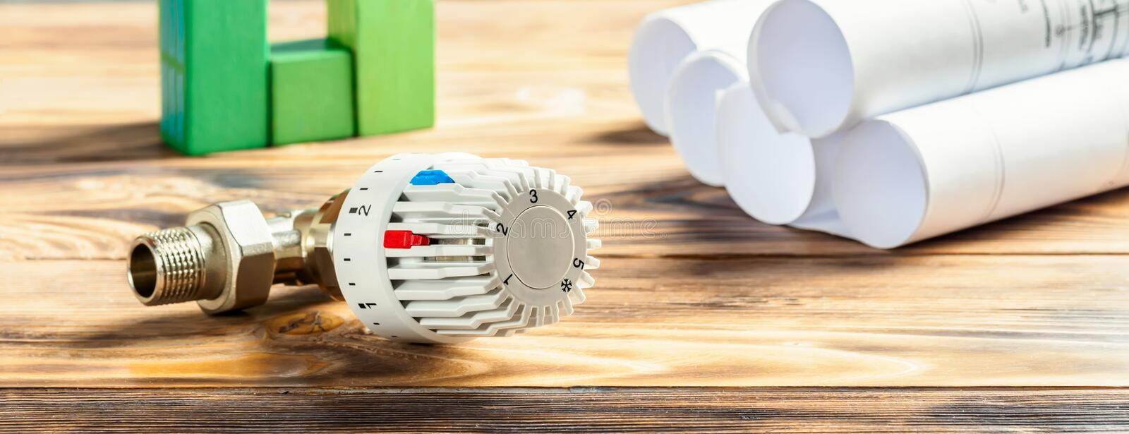 Concept of Energy saving. Thermostatic Head Valve for Radiator Heater and green house of cubes on wooden background Heating Project Heat Supply Building Concept stock photography