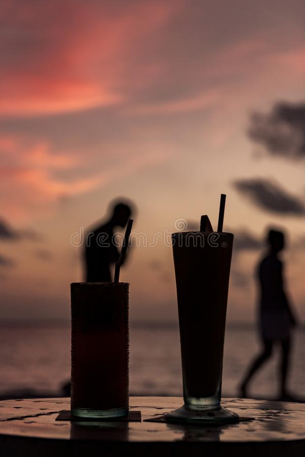Silhouette of two cocktail during sunset in a tropical island. people passing by in the background. Happy Hour royalty free stock image