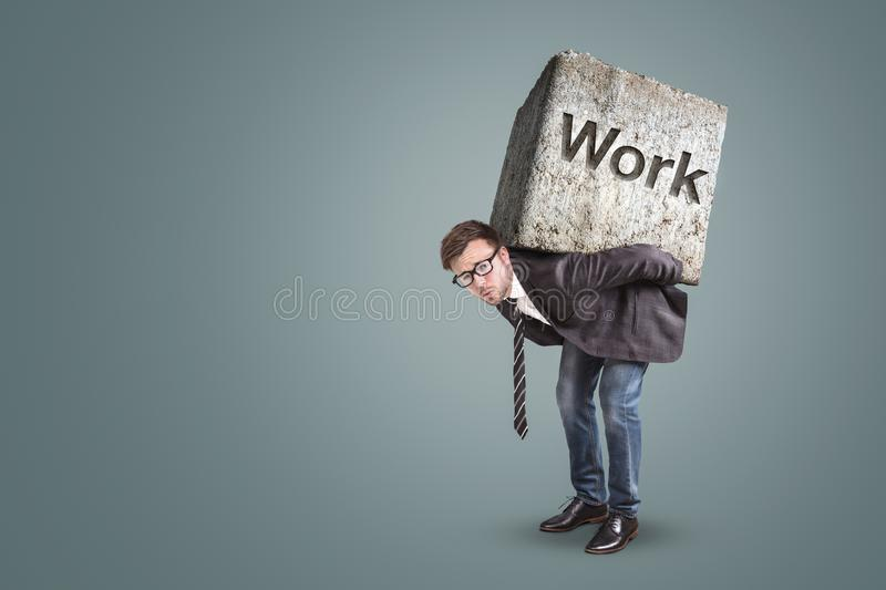 Concept of an entrepreneur bending under a heavy workload. He is actually carrying a massive stone with the word `Work` on it stock photography