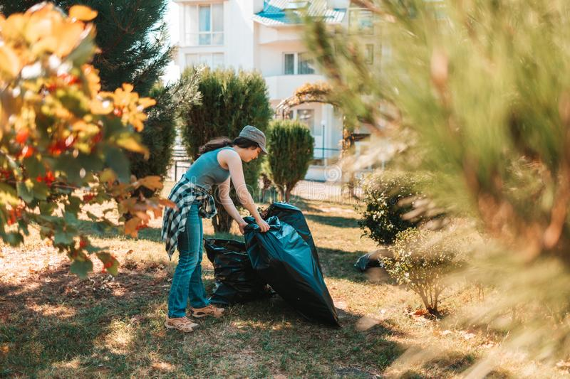 The concept of environmental pollution and Earth day. Woman volunteer doing cleaning in the Park in front of the house. She`s stock photo