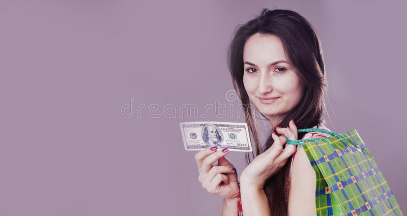 Concept: Everything has its own price. Image of a beautiful shocked happy woman with shopping bag holds US Dollar bill royalty free stock photos