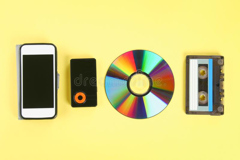 The concept of the evolution of music. Cassette, CD-disk, mp3 player, mobile phone. Vintage and modernity. Music support. royalty free stock photo