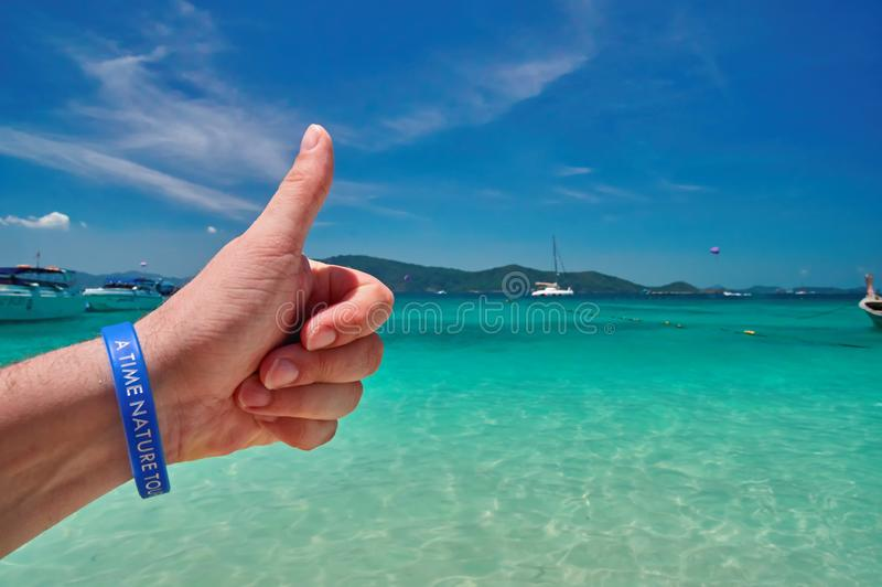 Concept excellent holiday at sea, landscape. Male hand with thumb up against turquoise sea and blue tropical sky Seascape tropical stock photo