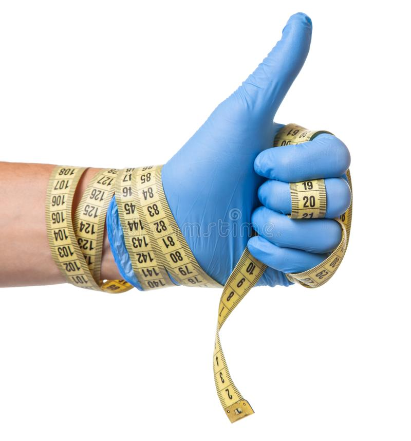 Concept of excess weight, weight loss, liposuction. Doctor in blue glove and measuring tape in his hands is isolated on white royalty free stock images