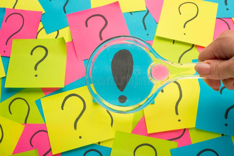 Concept with an exclamation point on a sticky note and magnifying glass royalty free stock photo