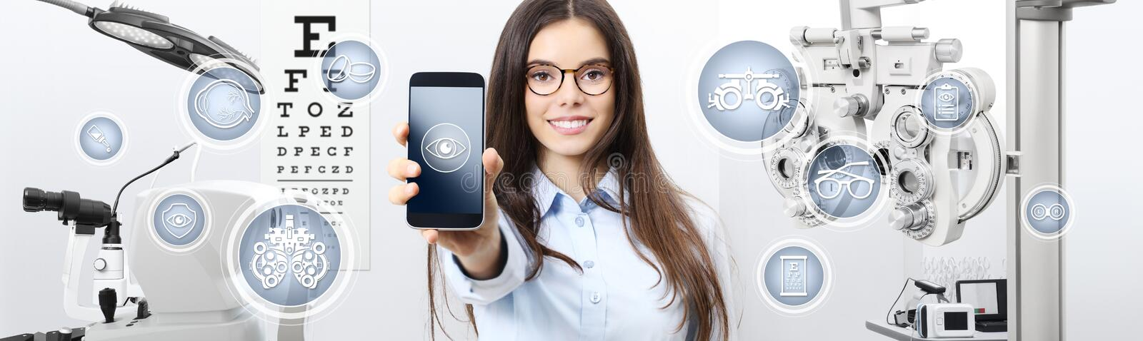 Concept of eye examination, smiling woman with spectacles showing mobile phone with icons in optometrist office, optician stock photography